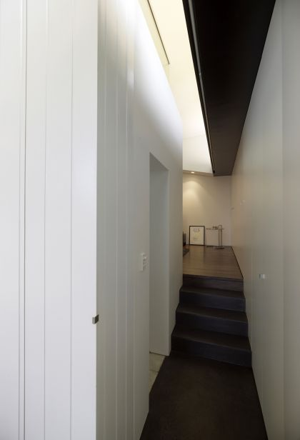 Haines House concrete stair passage, black ceiling & bathroom entry